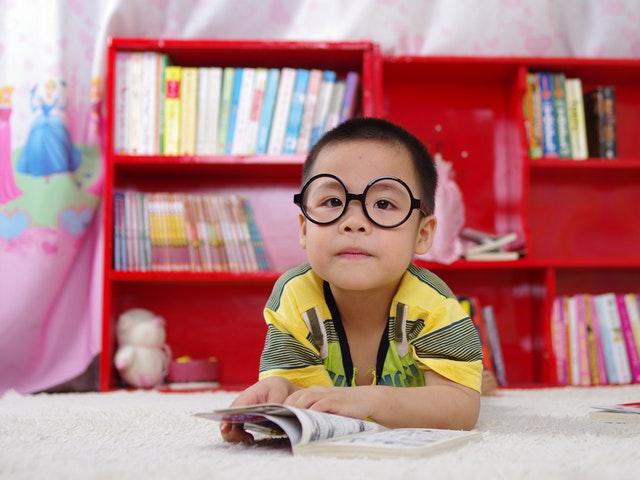 Liten pojke framför bokhylla